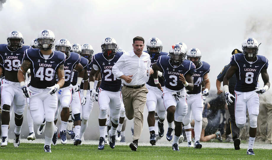 Connecticut head coach Bob Diaco, center, runs on the field with his team at the start of an NCAA college football game against Stony Brook at Rentschler Field, Saturday, Sept. 6, 2014, in East Hartford, Conn. (AP Photo/Jessica Hill)