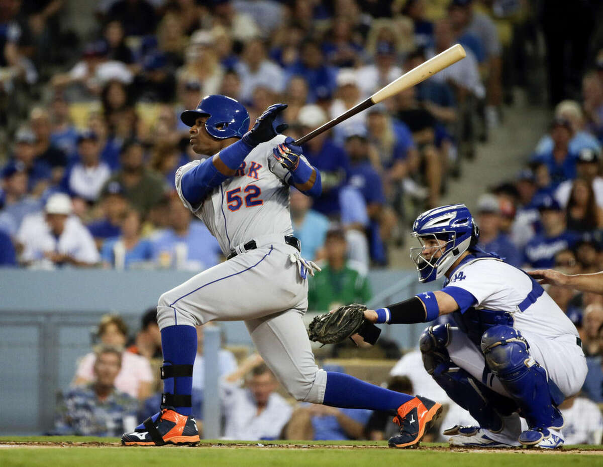 New York Mets' Yoenis Cespedes, left, watches his solo home run as Los Angeles Dodgers catcher Yasmani Grandal looks on during the second inning in Game 2 of baseball's National League Division Series, Saturday, Oct. 10, 2015 in Los Angeles. (AP Photo/Lenny Ignelzi)