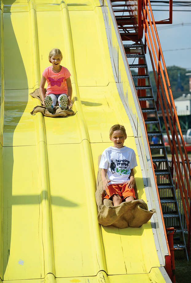 Hour photo / Erik Trautmann Walter and Grace Barsamian come down the Super Slide during the Norwalk Seaport Association's 37th annual Oyster Festival at Veteran's Park Saturday.