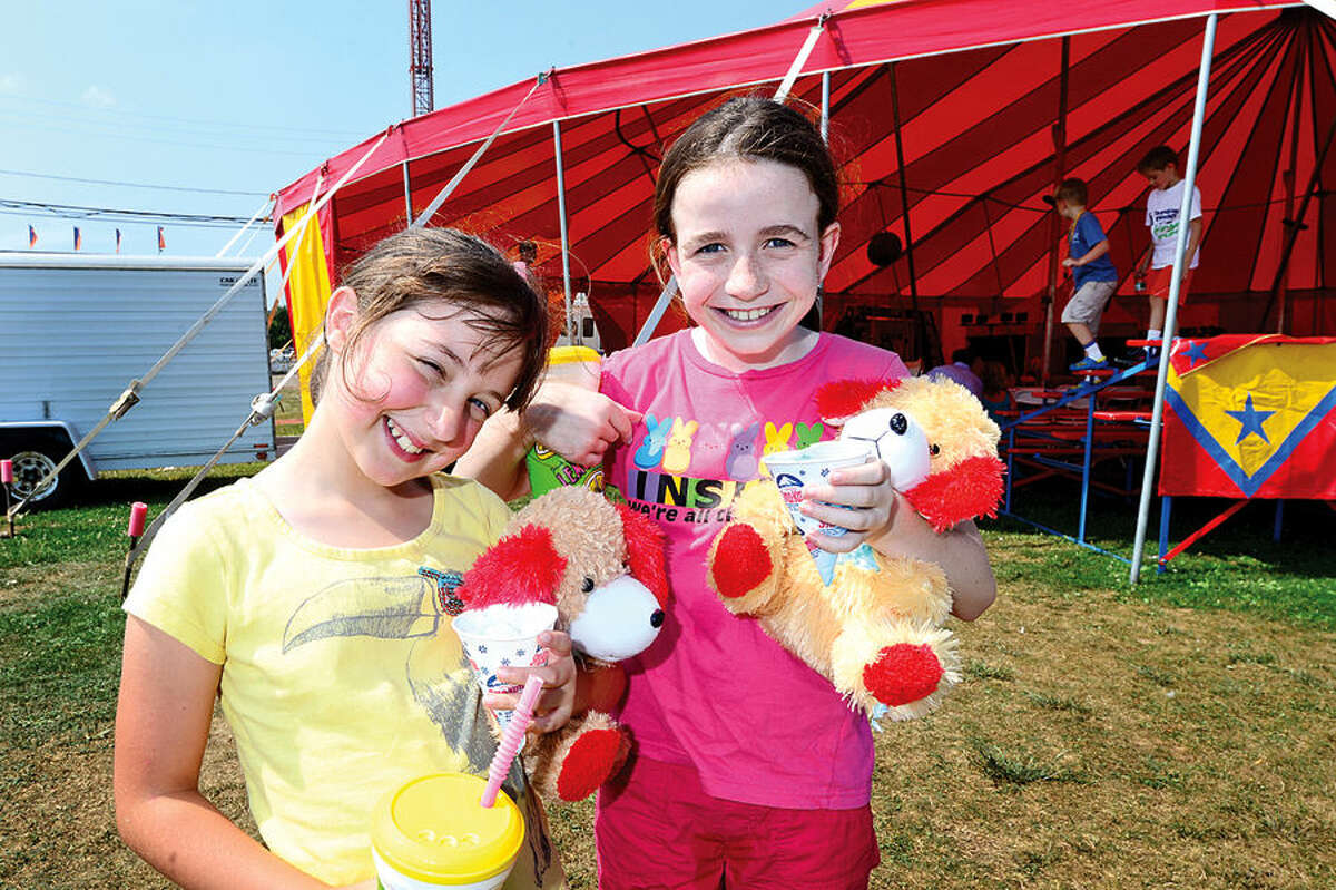 Hour photo / Erik Trautmann Isabella Rafalko and Bridget Downer, both 9, enjoy the Norwalk Seaport Association's 37th annual Oyster Festival at Veteran's Park Saturday.