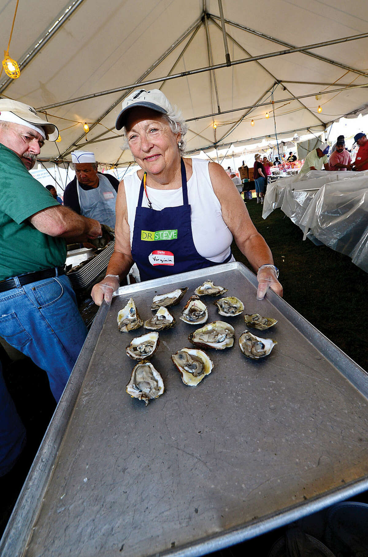 Hour photo / Erik Trautmann Virginia Lockwood serves up oysters from the Flotilla 72 Coast Guard Auxilliary tent during the Norwalk Seaport Association's 37th annual Oyster Festival at Veteran's Park Saturday.