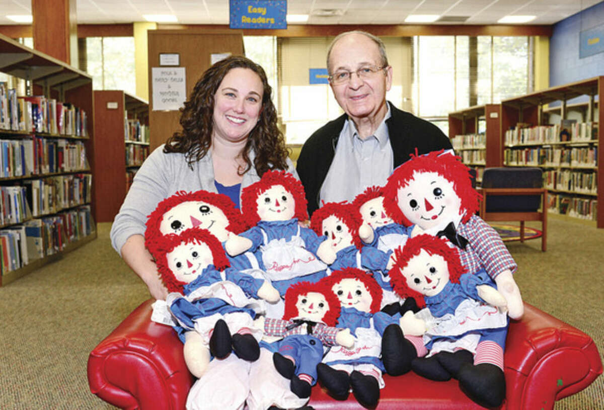 Hour photo / Erik Trautmann Vicky Oatis, Norwalk Public Library director of youth services, and Ralph Bloom, vice president of Friends of Norwalk Museums, Inc., are organizing a sale of the Museum's Raggedy Ann collection to benefit programming for the Norwalk Children's Library