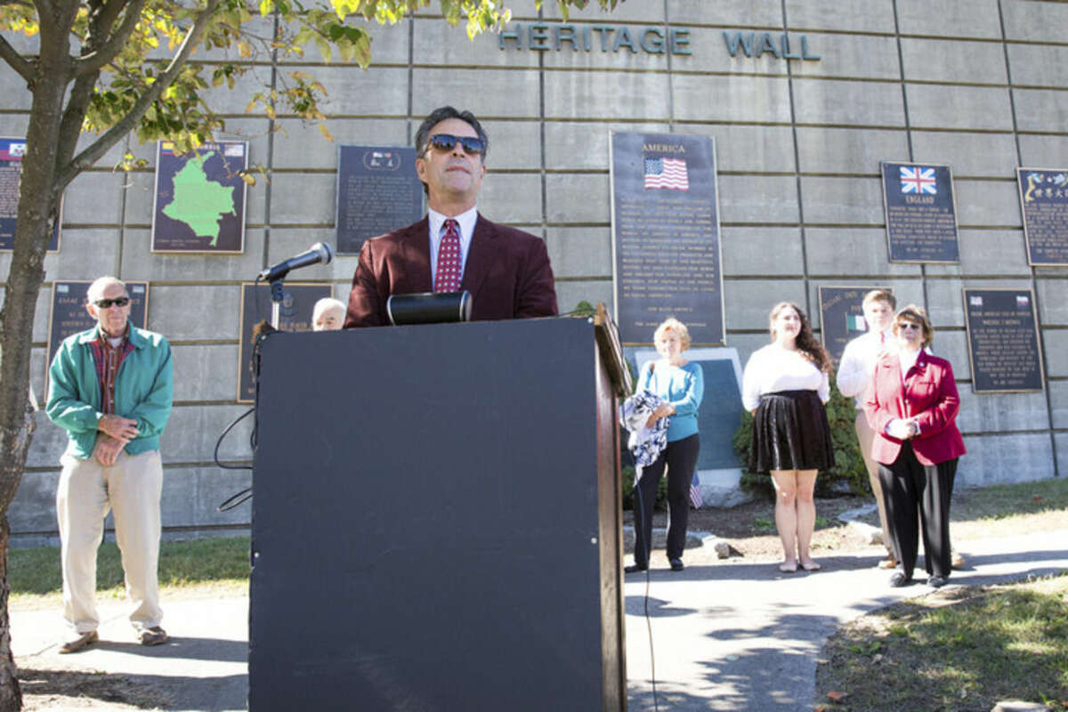 Hour photo/Chris Palermo Pat Catrone, chairman of the St. Ann Club board of directors, speaks at the Italian-American Day commemoration at Heritage Wall in Norwalk Sunday.