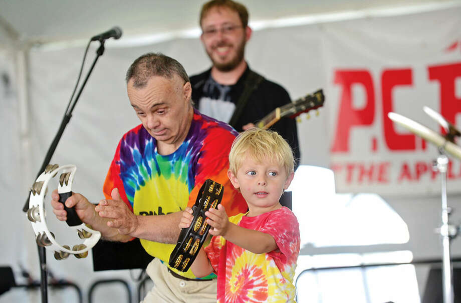 Hour photo / Erik Trautmann 4 year old Gibson Minnock joins MiMi Lesu and the Rubberband as part of The Hour's Battle of the Band's during the Norwalk Seaport Association's 37th annual Oyster Festival at Veteran's Park Saturday.