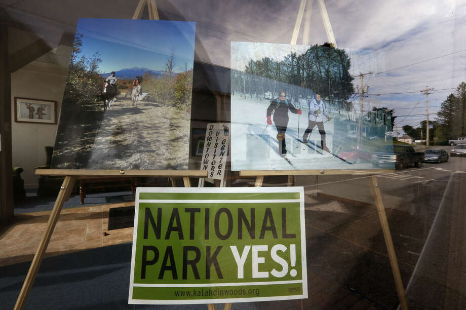 In this Sunday, Aug. 9, 2015, photo, photos promoting a proposed national park are seen in a downtown window front in Millinocket, Maine. Proponents of the national park proposal say they see growing support, and they're aiming for an aggressive timetable for making it a reality. (AP Photo/Robert F. Bukaty)