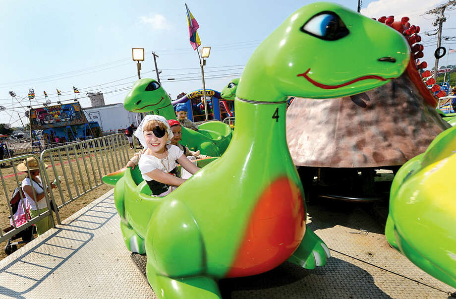 Hour photo / Erik Trautmann Ivy Heydte and her brothers, Lucian Heydte-Moorash and Leif Heydte-Moorash ride the dinosaur attraction during the Norwalk Seaport Association's 37th annual Oyster Festival at Veteran's Park Saturday.