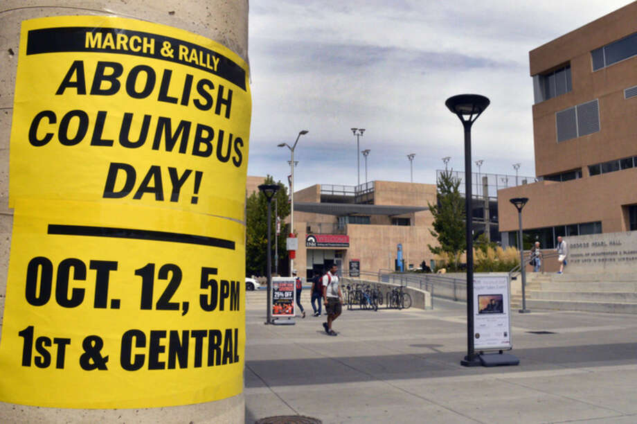 In this Sept. 21, 2015, photo, a flyer on the campus of the University of New Mexico in Albuquerque calls for students to join a protest against Columbus Day. Monday, Oct. 12, 2015, marks the annual Columbus Day nationwide, but in a twist that signals a growing trend, it will also be Indigenous Peoples Day in at least nine U.S. cities this year. (AP Photo/Russell Contreras)