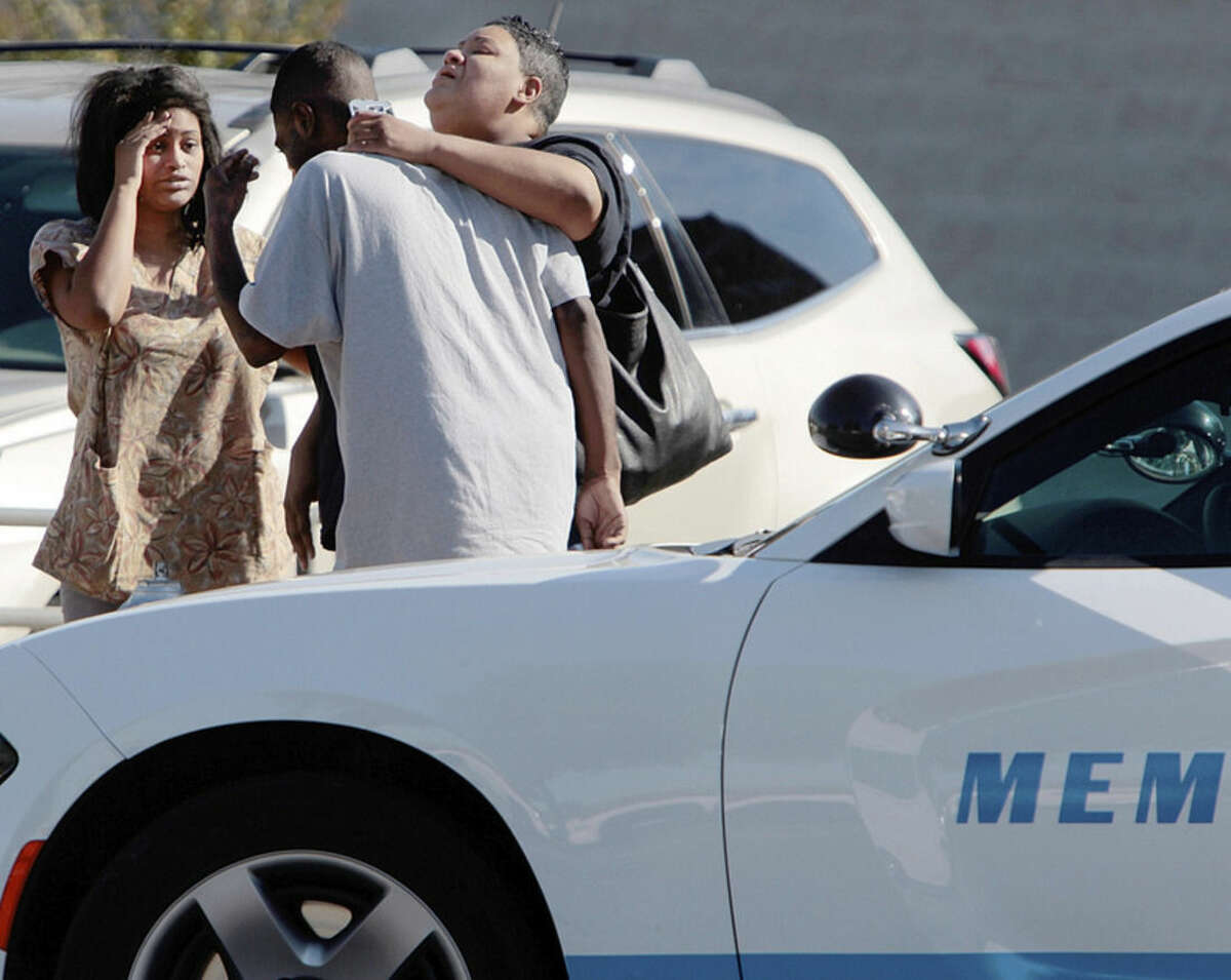 People wait outside the Regional Medical Center, Sunday, Oct. 11, 2015, in Memphis, Tenn. Memphis Police Director Toney Armstrong said Memphis Police Officer Terence Olridge was killed after being shot multiple times while off duty on Sunday. (Jim Weber/The Commercial Appeal via AP) MANDATORY CREDIT