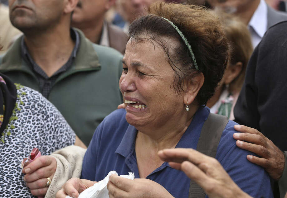 A protester is overcome with emotion during a rally to protest Saturday's explosions in Ankara, Turkey, Sunday, Oct. 11, 2015. Turkey declared three days of mourning following Saturday's nearly simultaneous explosions that targeted a peace rally in Ankara to call for increased democracy and an end to the renewed fighting between the Turkish security forces and Kurdish rebels. (AP Photo/Burhan Ozbilici)