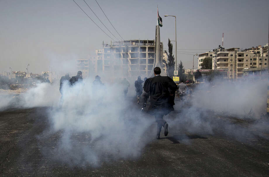 Palestinian lawyers Protesters run from tear gas fired by Israeli troops during a demonstration by scores of Palestinian lawyers called for by the Palestinian Bar Association in solidarity with protesters at the Al-Aqsa mosque compound in Jerusalem's Old City, near Ramallah, West Bank, Monday, Oct. 12, 2015. In recent weeks, at least 25 Palestinians, including nine attackers, have been killed by Israeli forces, while five Israelis have been killed in attacks. (AP Photo/Majdi Mohammed)