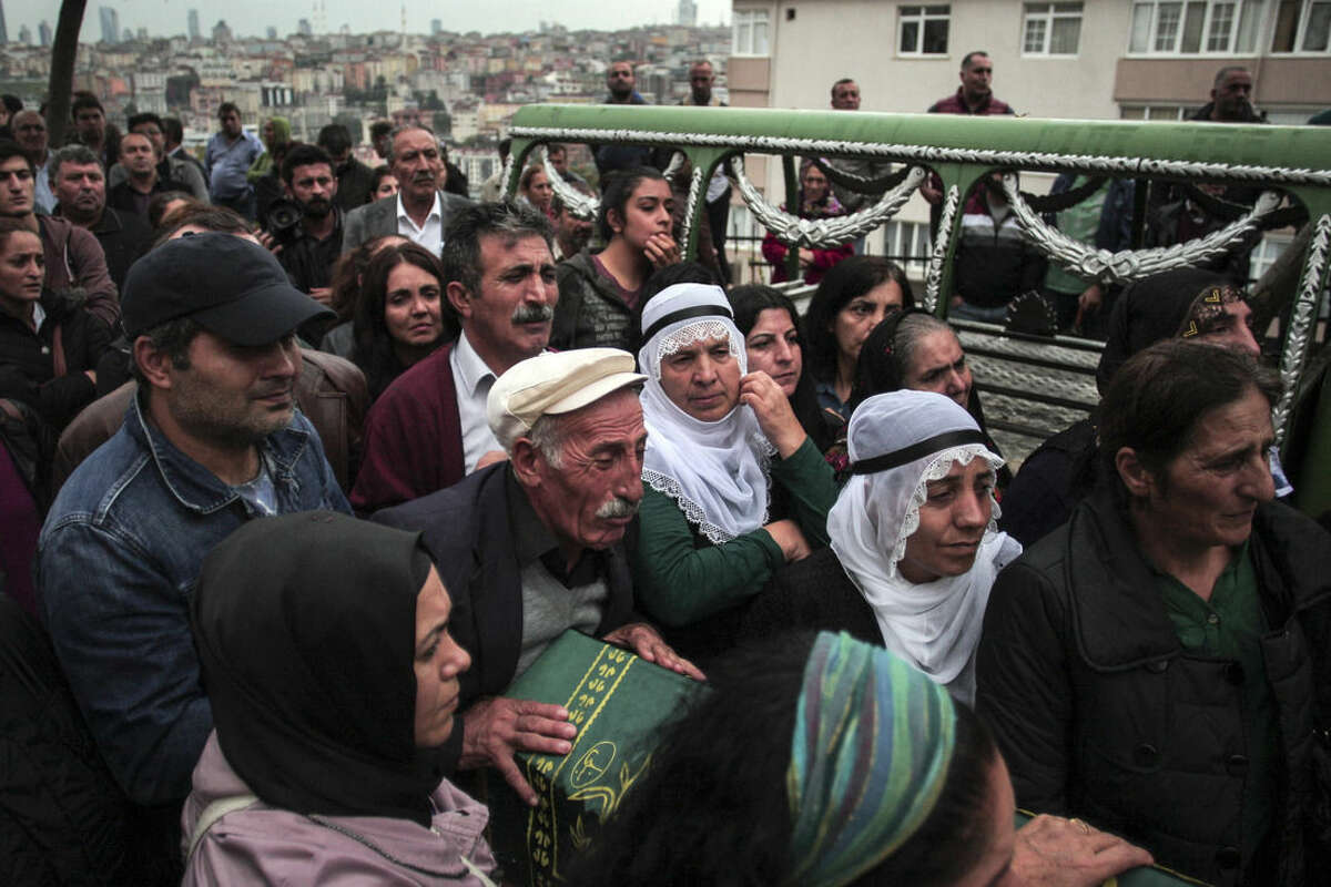 The father, centre, name not available of Sarigul Tuylu, 35, a mother of two that was killed in Saturday's bombing attacks in Ankara, Turkey, cries over her coffin during her funeral in Istanbul, Sunday, Oct. 11, 2015. Turkey declared three days of mourning following Saturday's nearly simultaneous explosions that targeted a peace rally in Ankara to call for increased democracy and an end to the renewed fighting between the Turkish security forces and Kurdish rebels. (AP Photo/Cagdas Erdogan)