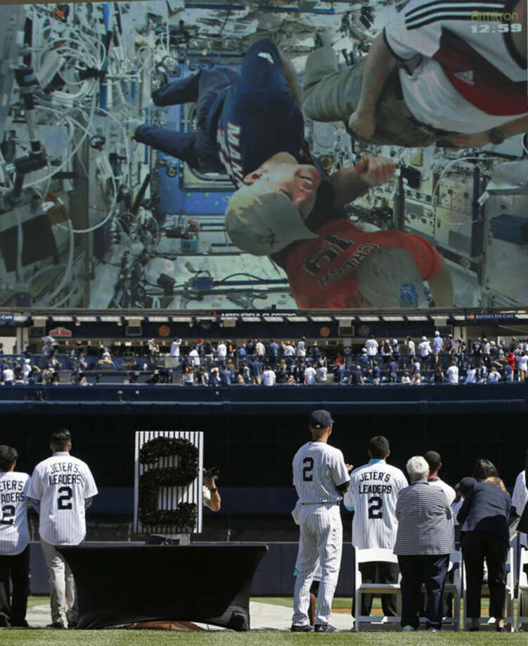 New York Yankees' Derek Jeter (2), right center, watches a video made by NASA astronauts on a giant video screen during a pregame ceremony honoring the Yankees captain, who is retiring at the end of the season, on Derek Jeter Day at Yankee Stadium in New York, Sunday, Sept. 7, 2014. (AP Photo/Kathy Willens)