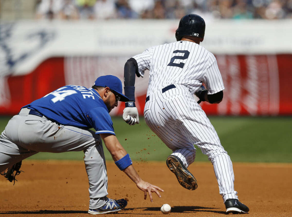 Kansas City Royals second baseman Omar Infante (14) loses the ball trying to tag out New York Yankees' Derek Jeter (2) on a ball hit by Martin Prado in the first inning of a baseball game at Yankee Stadium in New York, Sunday, Sept. 7, 2014. Prado reached first on the error, and Jeter was safe at second. Infante was changed with an error. (AP Photo/Kathy Willens)