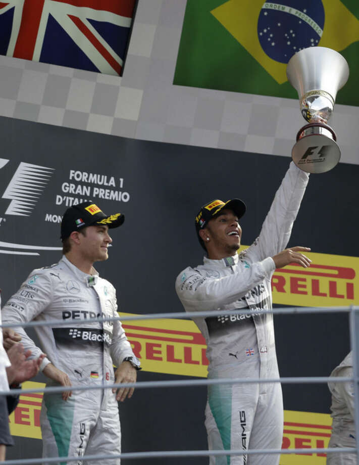 Britain's Lewis Hamilton celebrates on the podium flanked second place and teammate Germany's Nico Rosberg after taking his Mercedes racer to victory in the Italian Formula One Grand Prix at the Monza racetrack, in Monza, Italy , Sunday, Sept. 7 , 2014. (AP Photo/Luca Bruno)