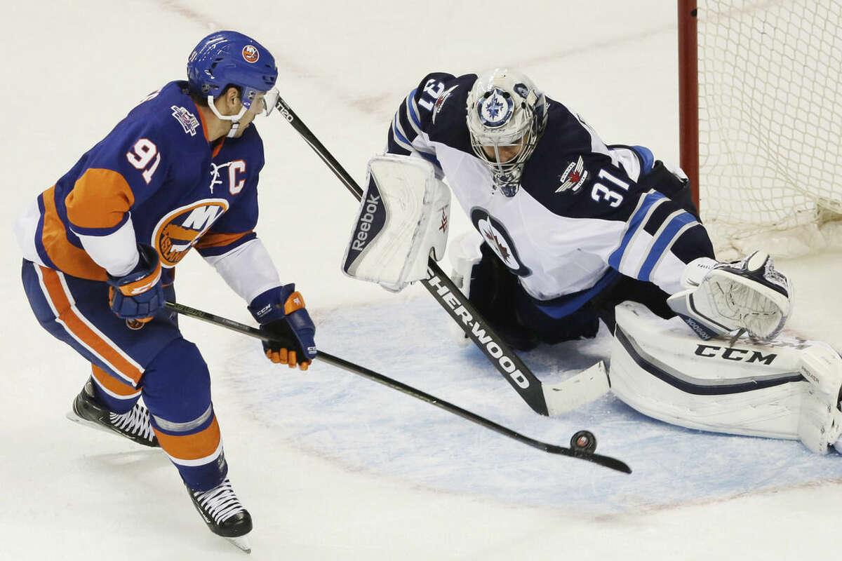 New York Islanders center John Tavares (91) misses a penalty shot against Winnipeg Jets goalie Ondrej Pavelec (31), of the Czech Republic, in the third period of an NHL hockey game, Monday, Oct. 12, 2015, in New York. The Islanders won 4-2. (AP Photo/Mark Lennihan)
