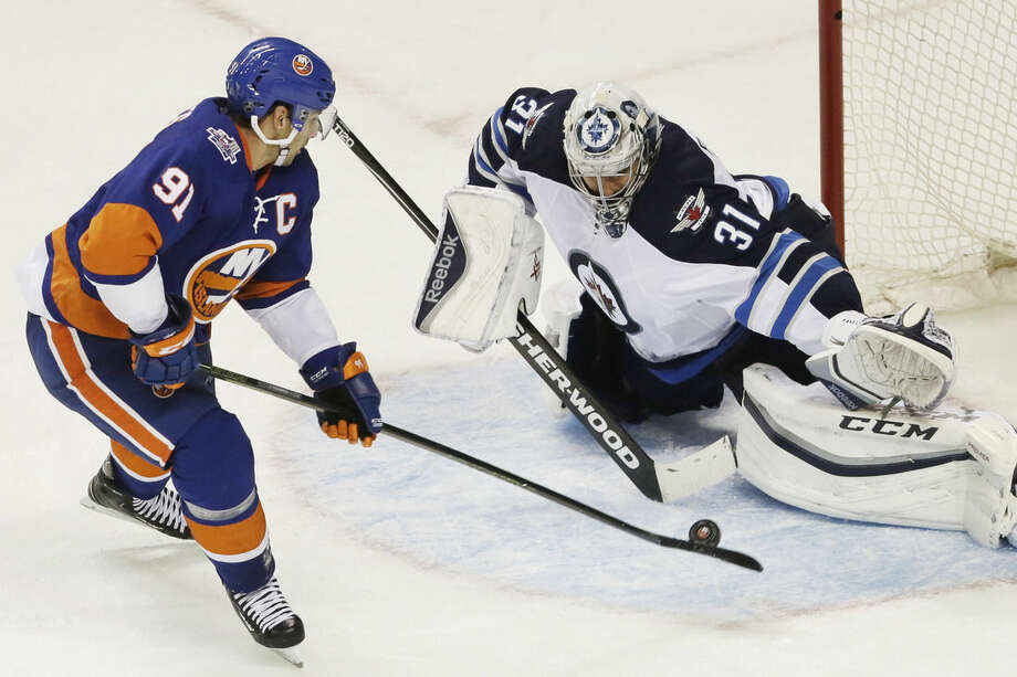 New York Islanders center John Tavares (91) misses a penalty shot against Winnipeg Jets goalie Ondrej Pavelec (31), of the Czech Republic, in the third period of an NHL hockey game, Monday, Oct. 12, 2015, in New York. The Islanders won 4-2. (AP Photo/Mark Lennihan)