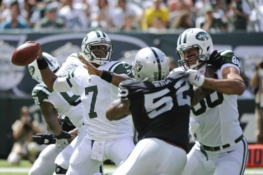 New York Jets quarterback Geno Smith (7) throws a pass as Jace Amaro (88) blocks Oakland Raiders' Khalil Mack (52) during the first half of an NFL football game Sunday, Sept. 7, 2014, in East Rutherford, N.J. (AP Photo/Bill Kostroun)
