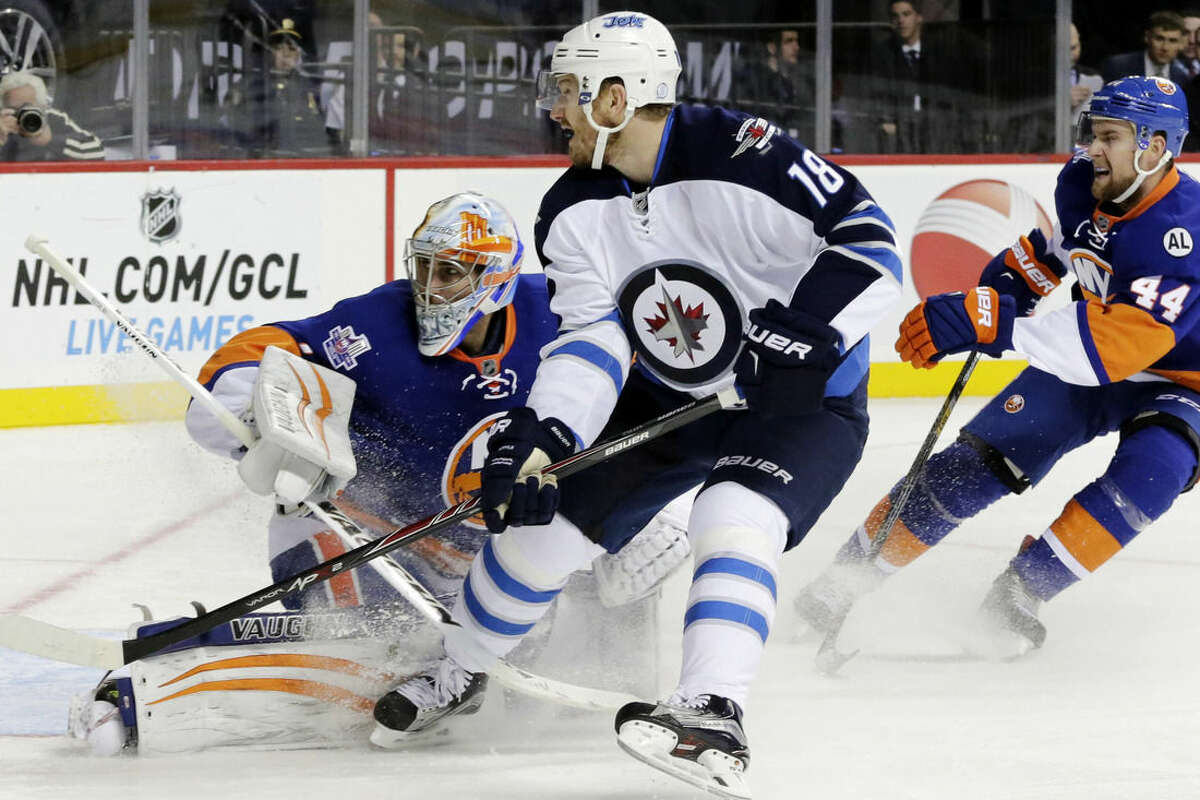 Winnipeg Jets center Bryan Little (18) misses a shot as he is defended by New York Islanders goalie Thomas Greiss, left, and defenseman Calvin de Haan (44) in the first period of an NHL hockey game, Monday, Oct. 11, 2015, in New York. (AP Photo/Mark Lennihan)