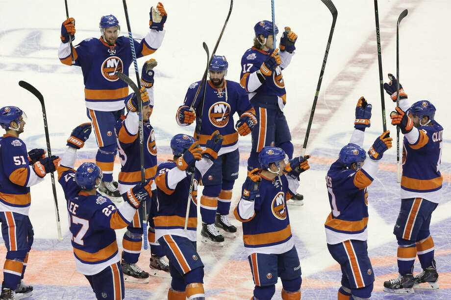 New York Islanders celebrate on the ice after defeating the Winnipeg Jets 4-2 in an NHL hockey game, Monday, Oct. 12, 2015, in New York. (AP Photo/Mark Lennihan)