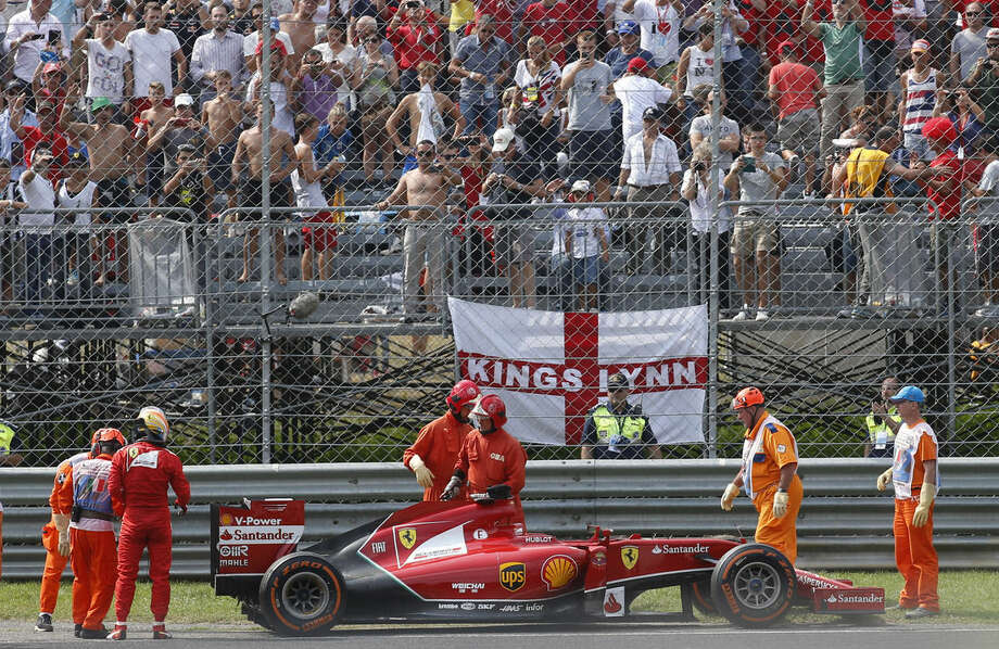 Ferrari driver Fernando Alonso of Spain watches his car after failing to complete the Italian Formula One Grand Prix, at the Monza racetrack, in Monza, Italy, Sunday, Sept. 7 , 2014. (AP Photo/Luca Bruno)