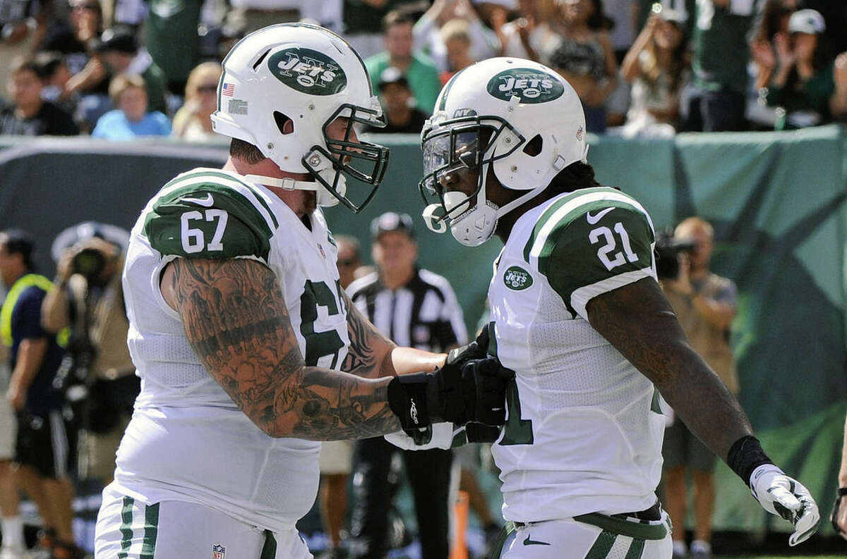 New York Jets' Chris Johnson (21) celebrates a touchdown with teammate Brian Winters (67) during the first half of an NFL football game against the Oakland Raiders, Sunday, Sept. 7, 2014, in East Rutherford, N.J. (AP Photo/Bill Kostroun)