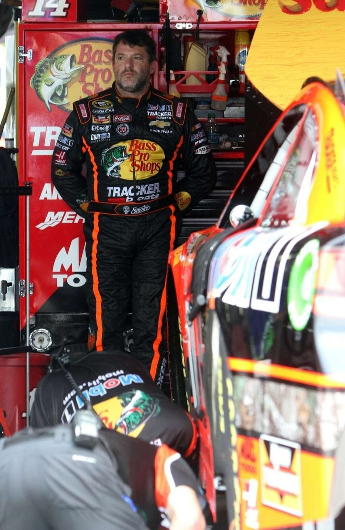 Driver Tony Stewart waits in the garage as his crew makes adjustments to his car during a practice session for Saturday night's NASCAR Sprint Cup series auto race at Richmond International Raceway, Friday Sept. 5, 2014, Richmond, Va. (AP Photo/Richmond Times Dispatch, Bud Kraft)