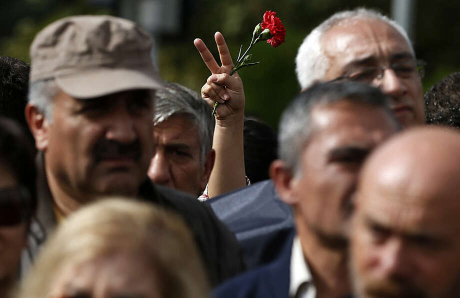 People participate in a memorial service for the victims of Saturday's attacks, at the site of the bombings in Ankara, Turkey, Monday, Oct. 12, 2015. The twin explosions Saturday ripped through a crowd of activists rallying for increased democracy and an end to violence between Kurdish rebels and Turkish security forces, killing dozens and injuring scores of others, in Turkey's deadliest attack in years. (AP Photo/Emrah Gurel)