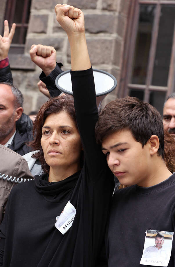 Emel Kitapci, the wife of Ali Kitapci, one of the victims from Saturday's bomb attacks, gestures as she stands with her son Artun Siyah Kitapci, 11, during a demonstration at the site of the explosions, in Ankara, Turkey, Monday, Oct. 12, 2015. Authorities investigating the twin suicide bombings at a rally promoting peace with the Kurdish were focusing on the Islamic State group, comparing DNA samples of the suspected bombers with those obtained from families of extremists they suspect could have carried out the attacks, a newspaper close to the government reported on Monday. The government meanwhile, raised the death toll in Turkey's deadliest attack in years to 97 and said the victims included a Palestinian. (AP Photo/Burhan Ozbilici)