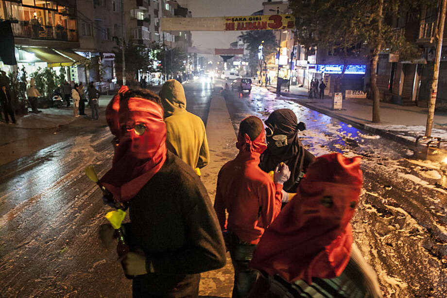 Masked leftist militants, one holding a Molotov cocktail, stand on a barricade during minor clashes with Turkish security forces during a protest against Saturday's Ankara bombing attacks, in Istanbul's Gazi district, Monday, Oct. 12, 2015. Turkish investigators were close to identifying one of the suicide bombers in Turkey's deadliest attacks in years, Prime Minister Ahmet Davutoglu said Monday. (AP Photo/Cagdas Erdogan)