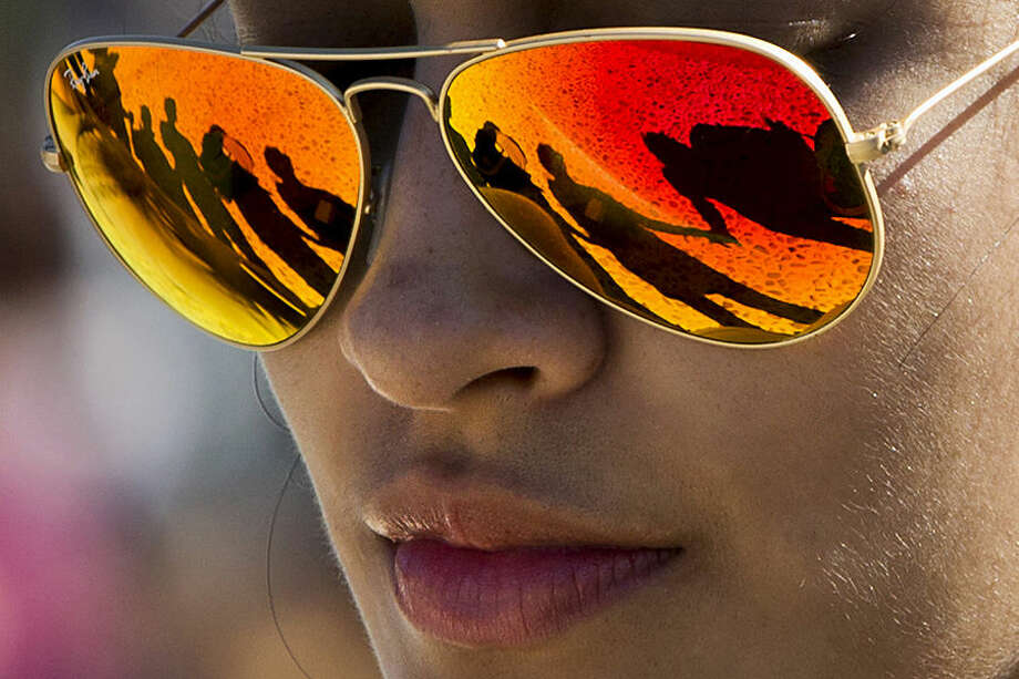 People holding hands in prayer are reflected in a woman's sunglasses during the Washington Prayer Gathering, with members from churches across Washington, Maryland, and Virginia joining in prayer, Monday, Oct. 12, 2015, at the Lincoln Memorial in Washington. (AP Photo/Jacquelyn Martin)