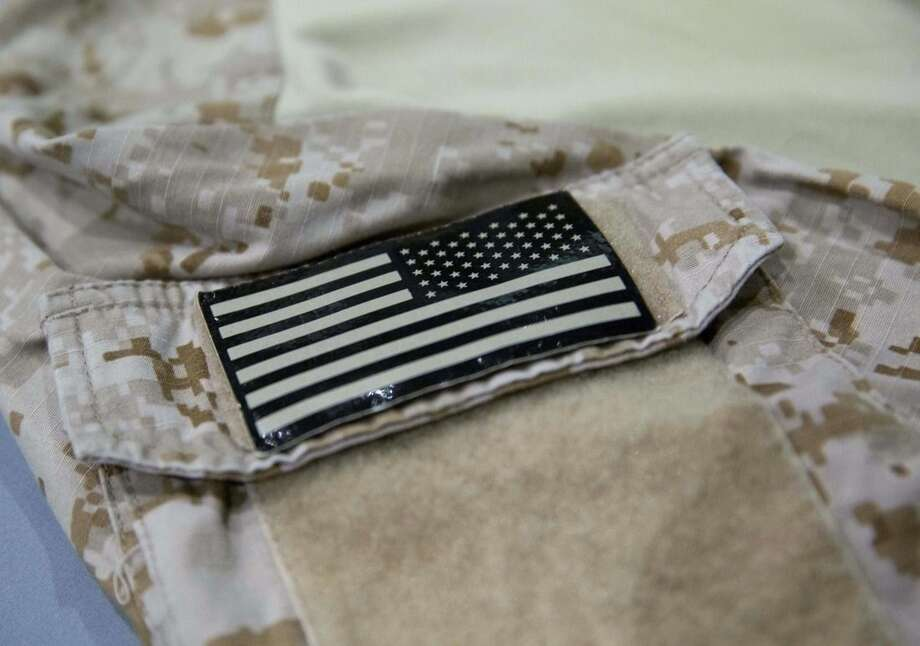 In this Sept. 5, 2014 photo provided by the National September 11 Memorial and Museum, a detail of the fatigue shirt showing an American flag emblem which worn by the U.S. Navy SEAL during the mission to capture Osama bin Laden, is seen in a case at the museum in New York. The shirt and other items from the raid will be introduced to the public on Sunday, Sept. 7.(AP Photo/National September 11 Memorial and Museum, Jin Lee)