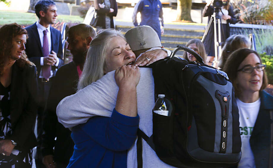 Umpqua Community College interim President Rita Cavin hugs an unidentified student on campus as the school reopens, Monday, Oct. 12, 2015, after being closed since the multiple fatality shooting on Oct. 1, in Roseburg, Ore. (Beth Nakamura/The Oregonian via AP, Pool)