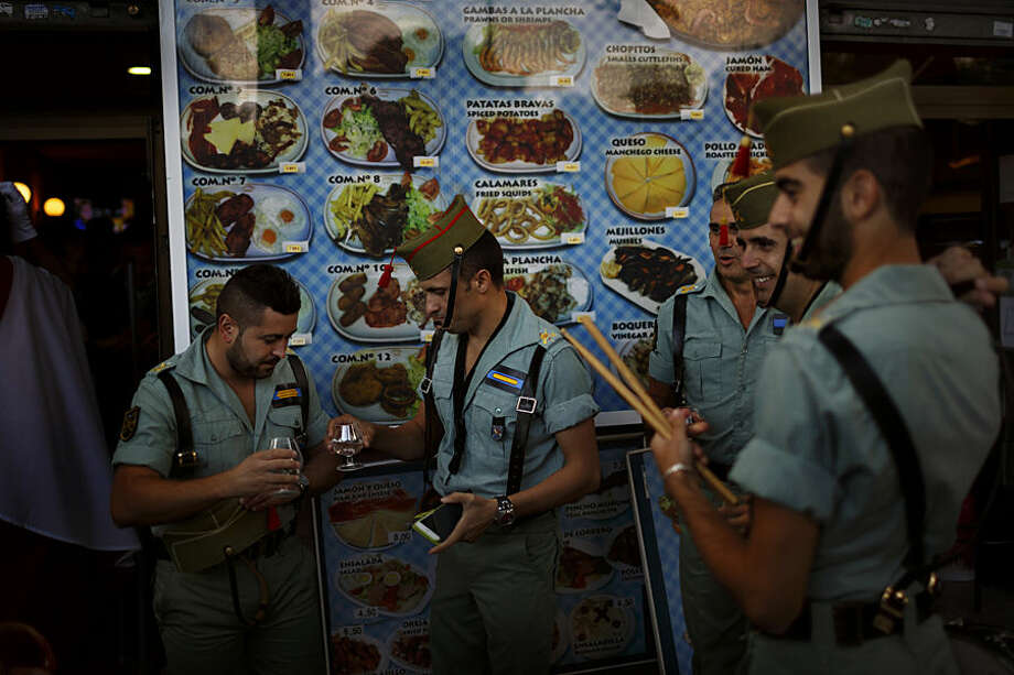 Members of La Legion, an elite unit of the Spanish Army, toast in a bar before a military parade as they celebrate a holiday known as 'Dia de la Hispanidad' or Spain's Hispanic Day in Madrid, Spain, Monday, Oct. 12, 2015. King Felipe has presided over a military parade celebrating Spain's National Day which 3,400 soldiers in crisp uniforms marched in central Madrid while armed forces aircraft performed a fly-past leaving trails of red and yellow smoke representing the Spanish flag. (AP Photo/Daniel Ochoa de Olza)