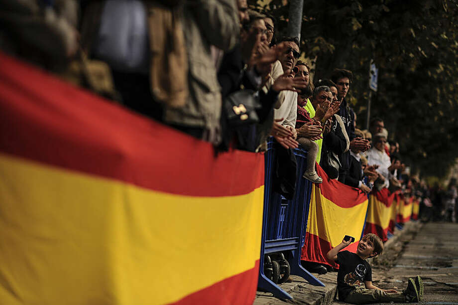 "EDS NOTE : SPANISH LAW REQUIRES THAT THE FACES OF MINORS ARE MASKED IN PUBLICATIONS WITHIN SPAIN. A young boy, bottom, reacts as he sits beside Spanish flags during an official holiday known as ""Dia de la Hispanidad"" or Spain's Hispanic Day in Pamplona, northern Spain, Monday, Oct. 12, 2015. The Monday holiday commemorates Christopher Columbus' arrival in the New World and is also Spain's armed forces day. (AP Photo/Alvaro Barrientos)"