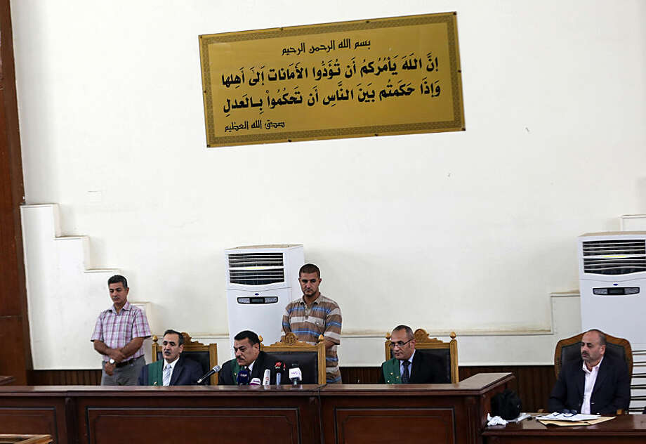 "Judges preside over a hearing involving Gamal and Alaa Mubarak, sons of deposed president Hosni Mubarak, at a courtroom in Tora Prison, Cairo, Egypt, Monday, Oct. 12, 2015. The court ordered the release of Gamal, Mubarak's one-time heir apparent, and his brother Alaa, a wealthy businessman, after time served on a corruption conviction. Many Egyptians view the brothers as key symbols of an autocratic and corrupt administration that struck an alliance with the mega-wealthy at the expense of the poor. Arabic verse from the Koran reads, ""Allah (God) orders you all to hand back trusts to their owners, and when you judge between people you judge with justice."" (AP Photo/Mohamed Elraai)"