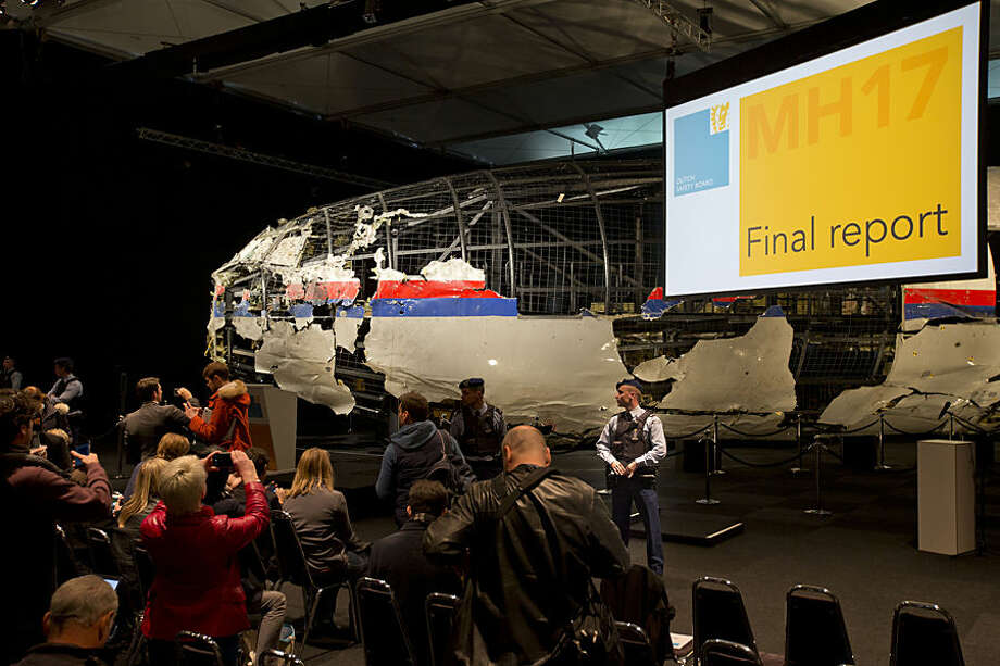 Part of the reconstructed Malaysia Airlines Flight 17 plane is seen prior to the presentation of the Dutch Safety Board presents the board's final report into what caused Malaysia Airlines Flight 17 to break up high over Eastern Ukraine last year, killing all 298 people on board, during a press conference in Gilze-Rijen, central Netherlands, Tuesday, Oct. 13, 2015. (AP Photo/Peter Dejong)