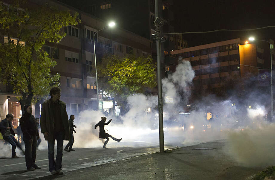 A protester kicks off a tear gas canister during clashes with Kosovo police in front of the central police station in Kosovo capital Pristina after the arrest of a prominent opposition politician Albin Kurti on Monday, Oct. 12, 2015. The main opposition parties have been protesting government's recent EU-sponsored deal with authorities in Serbia that give Kosovo's Serb minority greater rights in areas where they live. Albin Kurti, who is a leader of the nationalist Vetvendosje movement, set off a teargas canister inside Kosovo's Parliament in an attempt to halt the proceedings. (AP Photo/Visar Kryeziu)