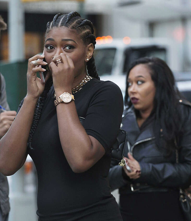 Cassie Frieson makes a phone call after leaving Motivo nightclub, Monday, Oct. 12, 2015, in New York. Frieson was in the club when she heard shots fired outside. Police say the shooting has left one woman dead and two others injured. Investigators are looking for the gunman after the bloodshed around 4 a.m. Monday in the Flatiron District. (AP Photo/Mark Lennihan)