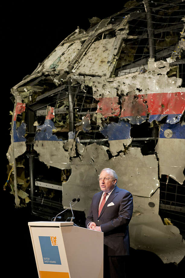 Tjibbe Joustra, head of the Dutch Safety Board, presents the board's final report into what caused Malaysia Airlines Flight 17, seen reconstructed rear, to break up high over Eastern Ukraine last year, killing all 298 people on board, during a press conference in Gilze-Rijen, central Netherlands, Tuesday, Oct. 13, 2015. (AP Photo/Peter Dejong)