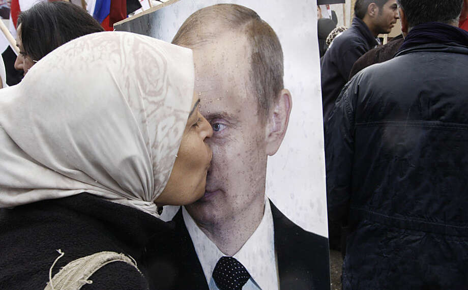 FILE - In this March 4, 2012 file photo, a Syrian woman kisses a poster of Russian President Vladimir Putin during a pro-Syrian government protest in front of the Russian Embassy in Damascus, Syria. Putin is winning plaudits from many Syrians and Iraqis, who see Russia's military intervention in Syria as a turning point after more than a year of largely ineffectual efforts by the U.S.-led coalition battling the Islamic State group. (AP Photo/Muzaffar Salman, File)