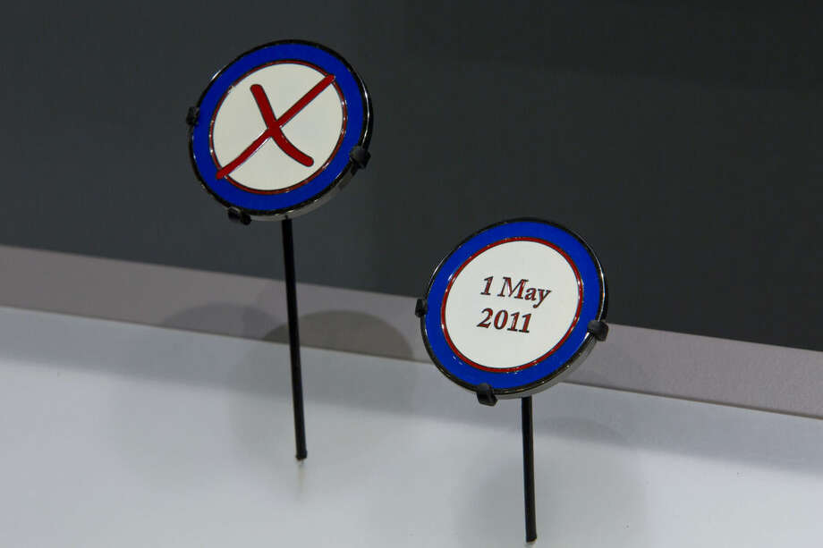 In this photo provided by the National September 11 Memorial and Museum, a special coin given to a CIA operative who played a key role in finding Osma bin Laden, is seen in a case at the museum on Friday, Sept. 5, 2014. The coin joins a fatigue shirt worn by a U.S. Navy SEAL wore in the raid that killed bin Laden. (AP Photo/National September 11 Memorial and Museum, Jin Lee)