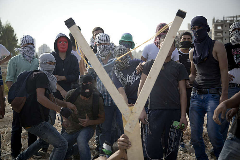 Palestinians uses a handmade large slingshot to hurl a stone during clashes with Israeli troops near Ramallah, West Bank, Monday, Oct. 12, 2015. Recent days have seen a series of stabbing attacks in Israel and the West Bank that have wounded several Israelis. Past weeks have also seen violent demonstrations in the West Bank and Gaza, and at least 16 Palestinians have been killed by Israeli forces. (AP Photo/Majdi Mohammed)