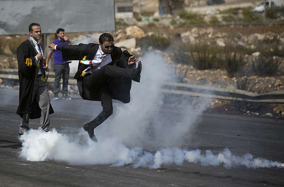 A lawyer wearing his official robes kicks a tear gas canister back toward Israeli soldiers during a demonstration by scores of Palestinian lawyers called for by the Palestinian Bar Association in solidarity with protesters at the Al-Aqsa mosque compound in Jerusalem's Old City, near Ramallah, West Bank, Monday, Oct. 12, 2015. In recent weeks, at least 25 Palestinians, including nine attackers, have been killed by Israeli forces, while five Israelis have been killed in attacks. (AP Photo/Majdi Mohammed)