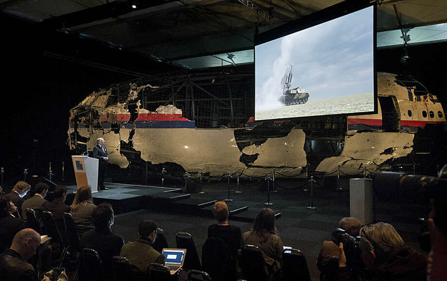 A video show the launch of a BUK missile, while a part of the reconstructed forward section of the fuselage is displayed behind, as Tjibbe Joustra, left, head of the Dutch Safety Board presents the board's final report into what caused Malaysia Airlines Flight 17 to break up high over Eastern Ukraine last year, killing all 298 people on board, during a press conference in Gilze-Rijen, central Netherlands, Tuesday, Oct. 13, 2015. (AP Photo/Peter Dejong)