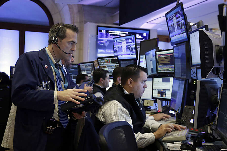 Trader Gregory Rowe, left, works with colleagues in their booth on the floor of the New York Stock Exchange, Monday, Oct. 12, 2015. Stocks are little changed in early trading as traders look ahead to the start of corporate earnings season. (AP Photo/Richard Drew)