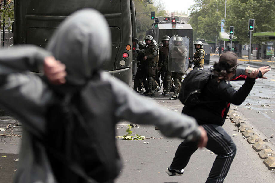 Masked protesters throw stones at police during a march against the commemoration of the discovery of the Americas in Santiago, Chile, Monday, Oct. 12, 2015. A small group clashed with police and attacked banks and a church. The march was organized by indigenous groups demanding autonomy and the recovery of ancestral land. Protesters also demonstrated against Chile's anti-terrorism law, under which many Mapuche Indians are under arrest. (AP Photo/Luis Hidalgo)
