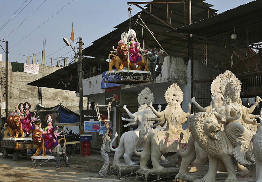 Indian workers bring an idol of Hindu Goddess Durga for Navratri, or nine nights festival celebrations, in Hyderabad, India, Monday, Oct. 12, 2015. Navaratri, the festival of nights, lasts for nine days, with three days each devoted to the worship of Durga, the goddess of valor, Lakshmi, the goddess of wealth, and Saraswati, the goddess of knowledge. Feasting and fasting takes over normal life for millions of Hindus, and many people join in religious dances in the evenings. The festival will begin from Oct. 13. (AP Photo/Mahesh Kumar A.)