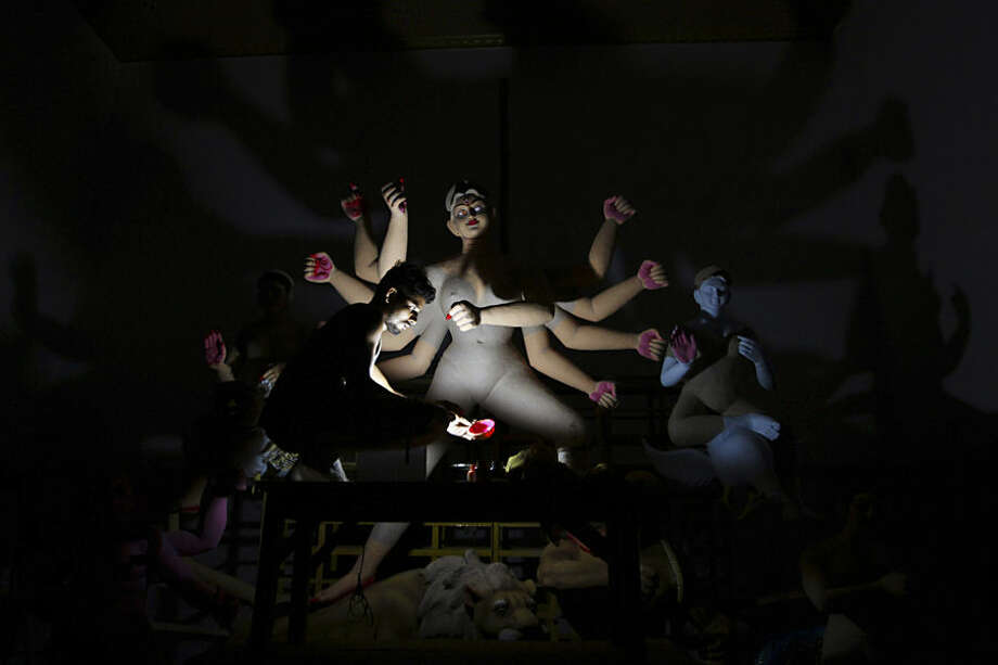 An artist colors a clay idol of Hindu goddess Durga in emergency torch light during a power cut at a worshipers' venue ahead of the Durga Puja festival, in the eastern Indian city Bhubaneswar, India, Monday, Oct. 12, 2015. he festival, to be celebrated from Oct. 19 to 22, commemorates the slaying of a demon king by lion-riding, ten armed goddess Durga, marking the triumph of good over evil. (AP Photo/Biswaranjan Rout)