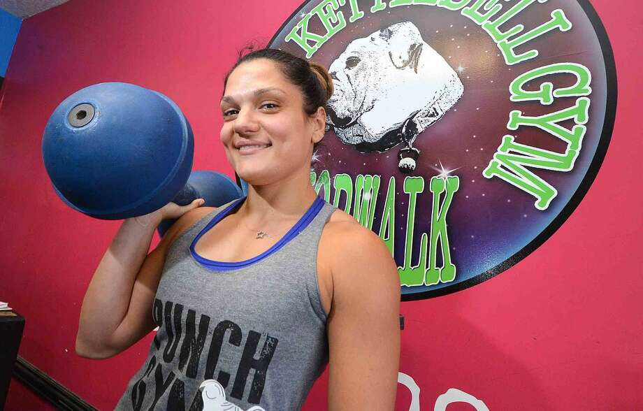 Owner Stefanie Tropea with a 50 pound circus dumbbell in her Punch Gym on Main Avenue in Norwalk.