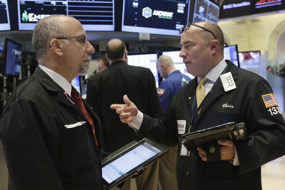 Traders John Liotti, left, and Christopher Morie confer on the floor of the New York Stock Exchange, Monday, Oct. 12, 2015. Stocks are little changed in early trading as traders look ahead to the start of corporate earnings season. (AP Photo/Richard Drew)